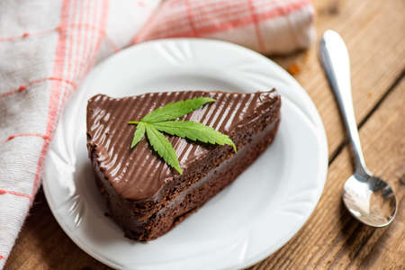 Chocolate cake with cannabis leaf - marijuana leaves plant on white plate on the wooden table, cannabis food nature herb concept
