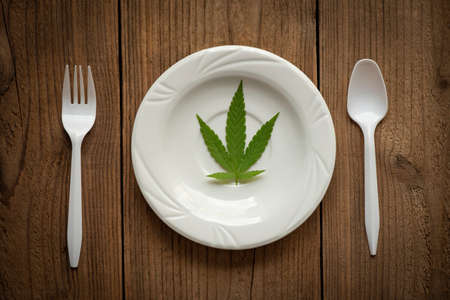Cannabis leaf - marijuana leaves plant on white plate on the wooden table and spoon fork, cannabis food nature herb concept