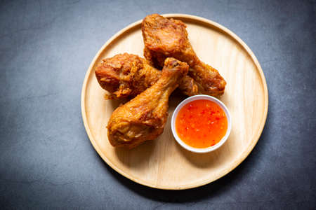 Fried chicken leg on plate with chicken dipping sauce, crispy fried chicken in a table food