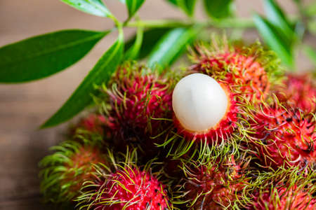 Fresh and ripe rambutan sweet tropical fruit peeled rambutan with leaves, Rambutan fruit on wooden background harvest from the garden 版權商用圖片