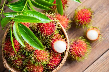 Fresh and ripe rambutan sweet tropical fruit peeled rambutan with leaves, Rambutan fruit on basket and wooden background harvest from the garden 版權商用圖片