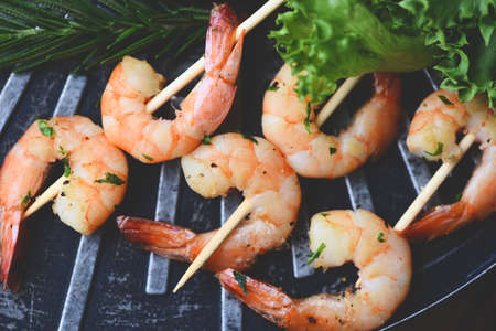 Grilled shrimp skewers seafood shelfish, Shrimps prawns with herbs garlic on the grill and vegetable lettuce