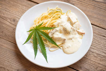 Cannabis food nature herb concept, Spaghetti carbonara on plate with cannabis leaf - marijuana leaves plant