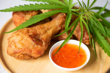 Cannabis food nature herb concept, Fried chicken leg on plate with chicken dipping sauce, crispy fried chicken food with cannabis leaf - marijuana leaves plant