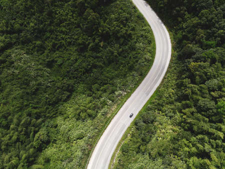 Aerial view forest nature with car on the road on the mountain green tree, Top view road curve from above, Bird eye view road through mountain the green forest beautiful fresh environment