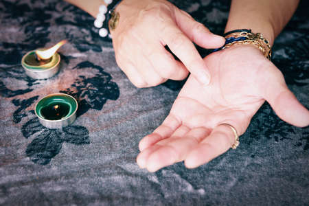 Show fortune tellers of reading palms, and performing readings with candle light, Palmistry fortune teller reads lines on hand Performing readings magical performances, Things mystical astrologists