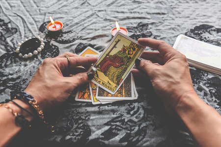 Show fortune tellers of hands holding tarot cards and tarot reader with candle light on the table, Performing readings magical performances, Things mystical astrologists forecasting concept Zdjęcie Seryjne