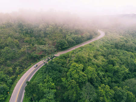 Aerial view foggy road forest tree environment nature background, mist on green forest top view foggy landscape the hill from above, wood tree road curve to mountain background Zdjęcie Seryjne
