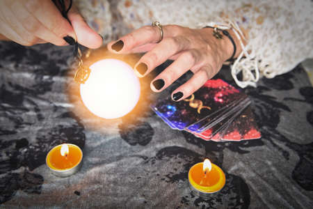 Show fortune tellers of hands holding tarot cards and tarot reader with candle light and magic Crystal ball, Performing readings magical performances, Things mystical astrologists forecasting concept