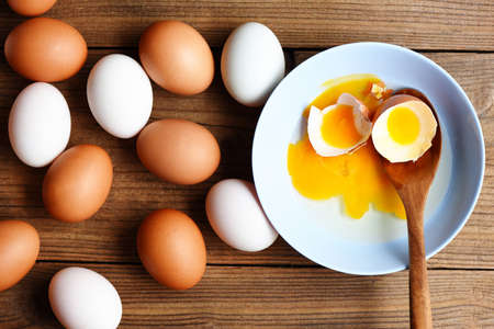 Chicken eggs and duck eggs collect from farm products natural on wooden healthy eating concept,  Fresh broken egg yolk