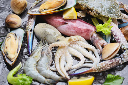 Seafood shellfish on ice frozen with shrimps prawns crab claws shell clam squids octopus and mussels at the restaurant, Fresh raw seafood buffet with lemon rosemary ingredients herb and spices