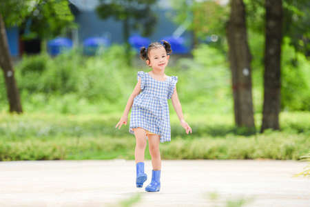 Asian kid girl happy in the park garden tree background, Beautiful child having fun playing outside with happy smile children playing outdoors little girl portrait wear colorful boots