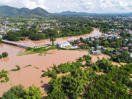 Aerial view river flood village countryside Asia and forest tree, Top view river with water flood from above, Raging river running down jungles lake flowing wild water after the rain