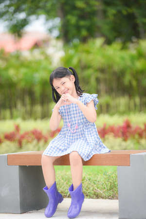 Asian kid girl happy in the park garden tree background, Beautiful child having fun playing outside with happy smile children playing outdoors little girl portrait wear colorful boots sitting bench