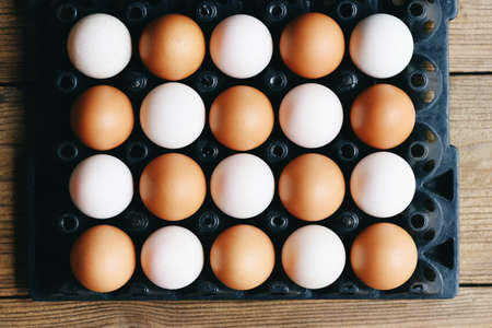 Fresh chicken eggs and duck eggs in egg box on wooden table background, light and shadow concept