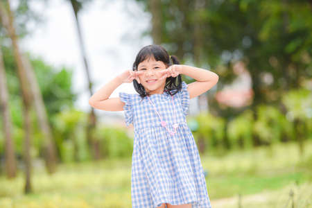Asian kid girl happy in the park garden tree background, Beautiful child having fun playing outside with happy smile children playing outdoors little girl portrait.