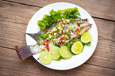 Steamed tilapia fish with chili and lime lemon sauce with herb and Vegetable on plate, Fish steam lime - Thai food Stockfoto