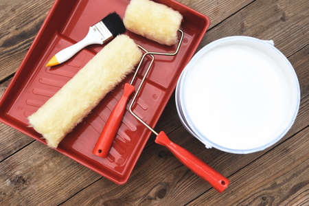 Painted tool with roller paint brush paint bucket canned paint for painting on wooden background, top view on paint tray