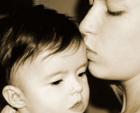 infancy: Mother kissing her baby Stock Photo