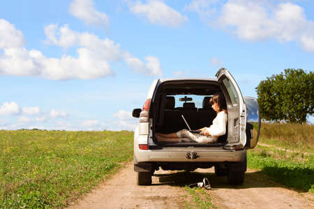 industrie: Young girl with laptop in a car