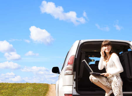 Young girl with laptop and phone in car photo