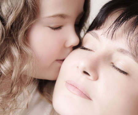 kisses: Child kissing her mother