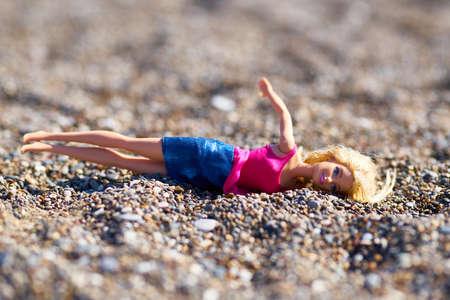 Fallen doll in the sand
