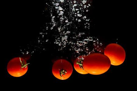 Red tomato on black background with water splash Stok Fotoğraf