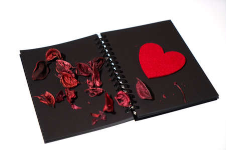 Dry roses petals with red heart shape on a black book. Valentines concept.