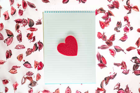 Valentines day background with a blank notepad, red heart shape and rose petals Stok Fotoğraf