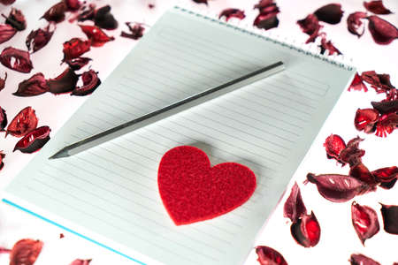 Valentines day background with a pencil, blank notepad, red heart shape and rose petals