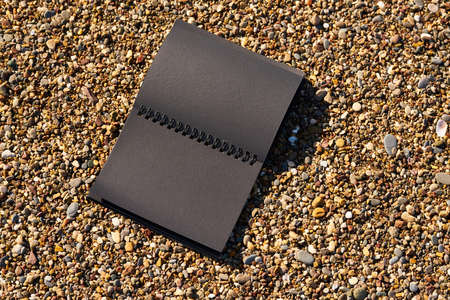 Blank black notebook on the sand at the seashore
