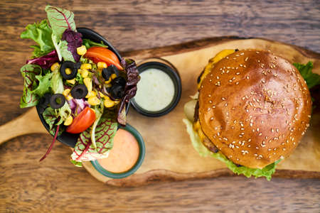 Cheeseburger with salad on the wooden table