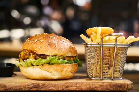 Cheeseburger with french fries on the wooden table
