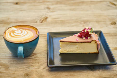 Delicious latte coffee and cheesecake on the wooden table