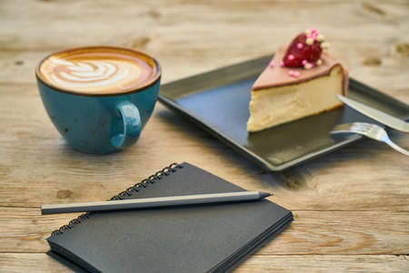 Latte coffee, cheesecake and notebook on the table Stok Fotoğraf - 126047173