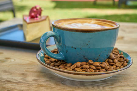 Latte coffee, coffee beans and cheesecake on the wooden table