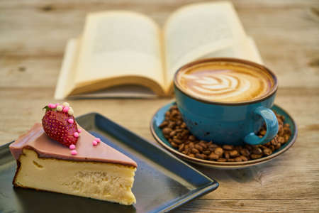 Latte coffee, coffee beans, cheesecake and book Stok Fotoğraf