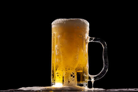 A cold fresh beer in front of a black background