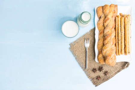 gressins: Gressins et lait sur fond de table bleu ciel.Snack avec repas ou de la nourriture de détente et de vacances. Vue de dessus.