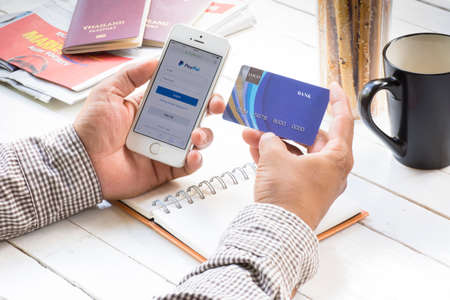 paypal: Credit card and smartphone- August 1 ,Man holding cradit card and smartphone and open paypal site for payment online for traveling plan for relax in holiday.