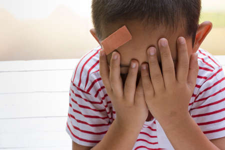 elbow band: Child wound on head with wooden white background,Top view and zoom in