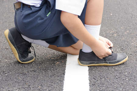 lacing sneakers: Childs student  tying shoes at roadside. Stock Photo