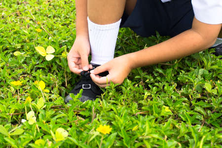 Child student  tying shoes in the park of school.