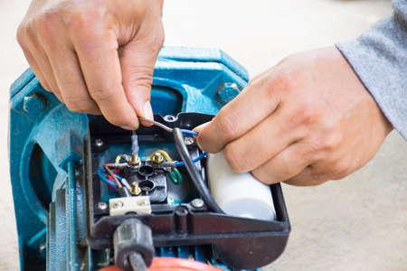 Moteur électrique et homme travaillant réparation de l'équipement sur le plancher de ciment background.Background moteur ou equipment.Close up. Banque d'images