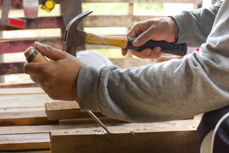 stillife: Carpenter using  chisel and hammer in his hand with plank.Close up and stillife.