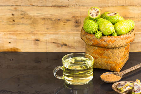noni: Noni fruit  and noni juice with noni powder on black table.Fruit for health and herb for health. Stock Photo