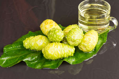 Noni fruit  and noni juice on black table.Fruit for health and herb for health.