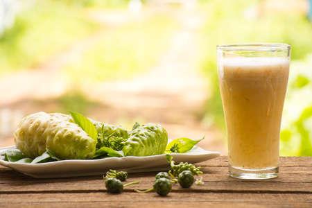 木製の背景にノニジュースとノニのジュース。健康や健康のためのフルーツやハーブの健康のためのジュース。屋外の眺め