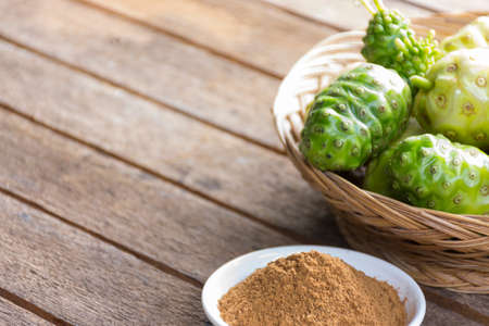 noni: Noni fruit  and  noni powder on wooden table.Fruit for health and herb for health. Stock Photo